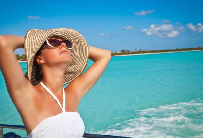Young beautiful women dreaming on the deck of a yacht at Caribbean sea. Woman resting on the water. Summer cruise holidays