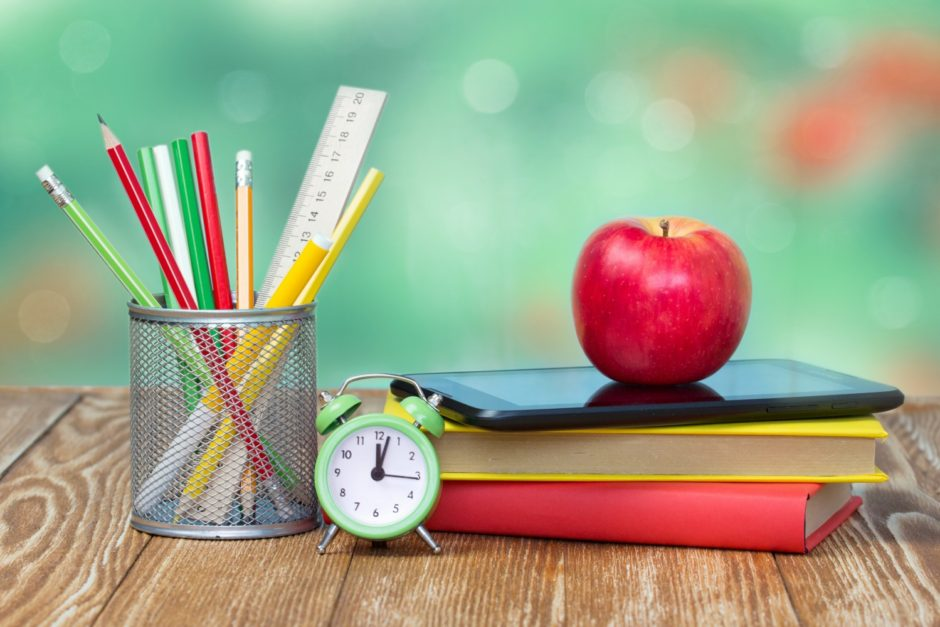 School supplies on wooden table desk nature green background empty space.Apple stack books stationary alarm back to school concept.